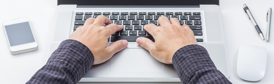 A woman's finger presses a key on a clean laptop keyboard.